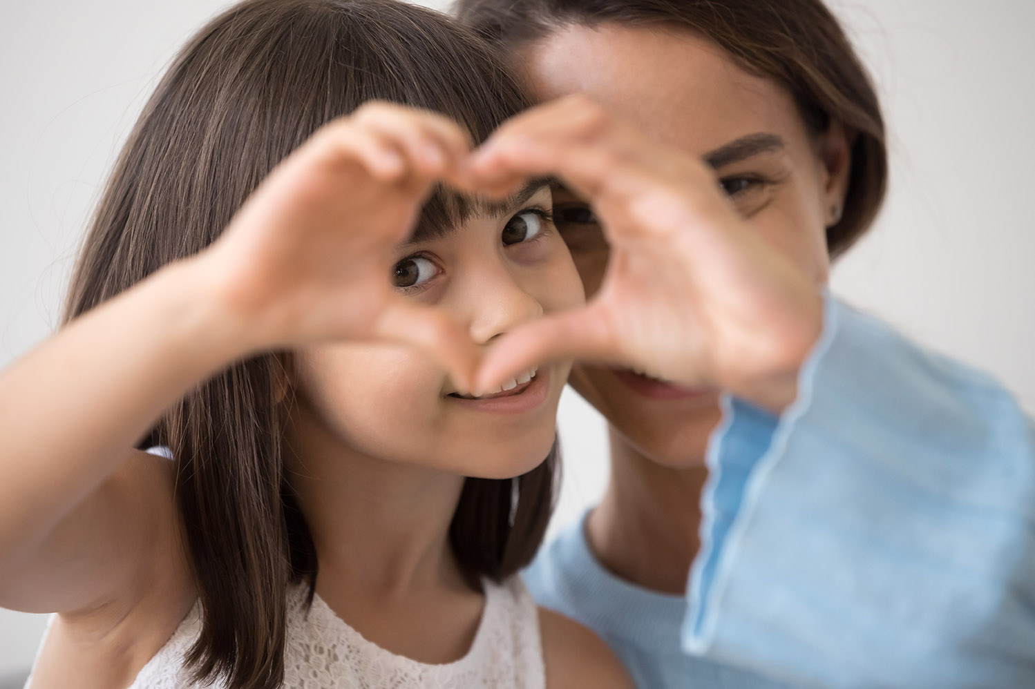 Little girl and mom creating a heart shape to thank donors